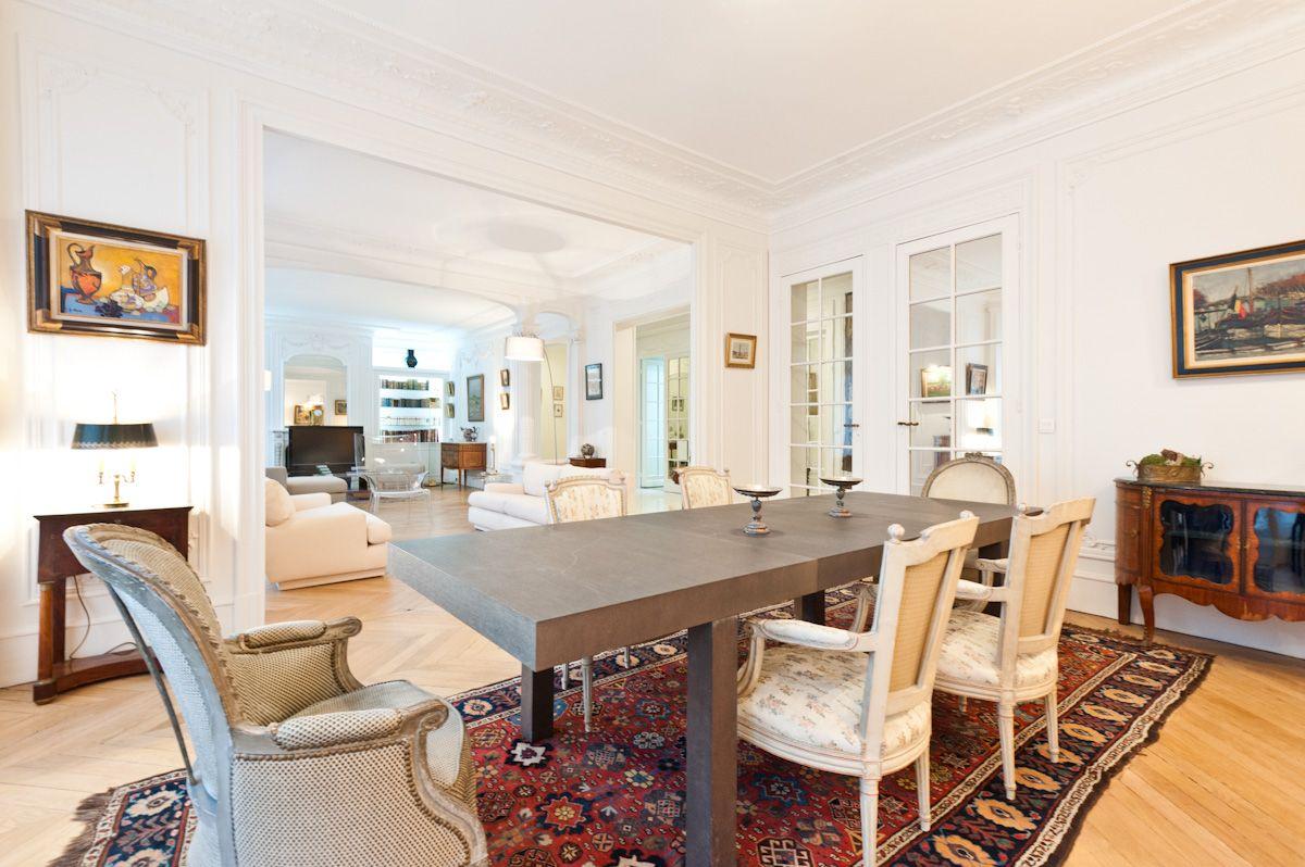 salle manger dun appartement haussmannien la table diner est contemporaine agrmente de chaises anciennes le tout reposant sur un tapis ancien