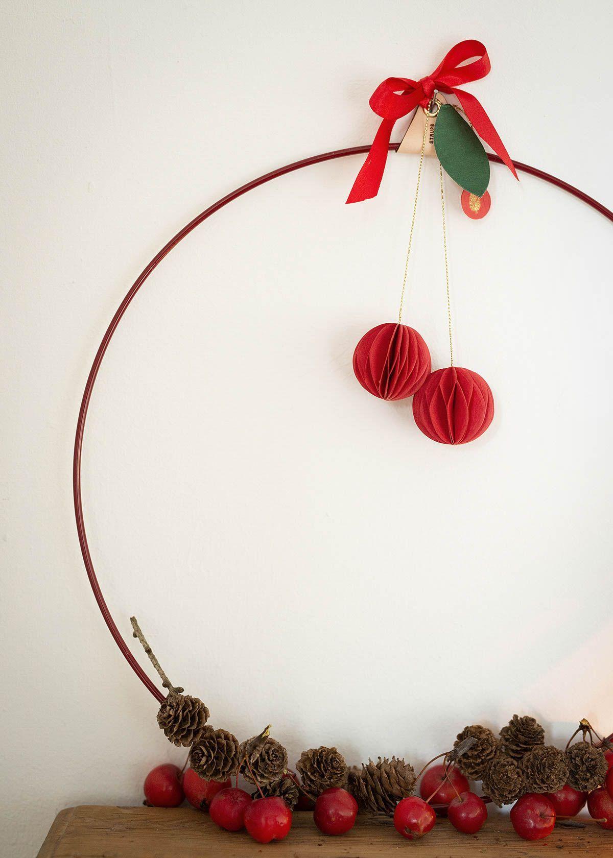 Wunderschön gemacht - #weihnachtsdeko2019trend Der schlichte Dekoring in rot ist mit Zapfen, Zieräpfeln und den Rosetten- Papieräpfeln dekoriert. Den Metallkranz, die Honeycomb Apfel-Christbaumhänger und die Eichhörnchen sind im wunderschoen-gemacht shop erhältlich. #weihnachtsdeko #adventskranz #kranzmitäpfeln #wunderschoengemachtblog #wunderschoengemachtshop