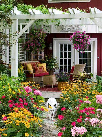 Un patio fiorito e una casa con un bellissimo contrasto rosso scuro/bianco