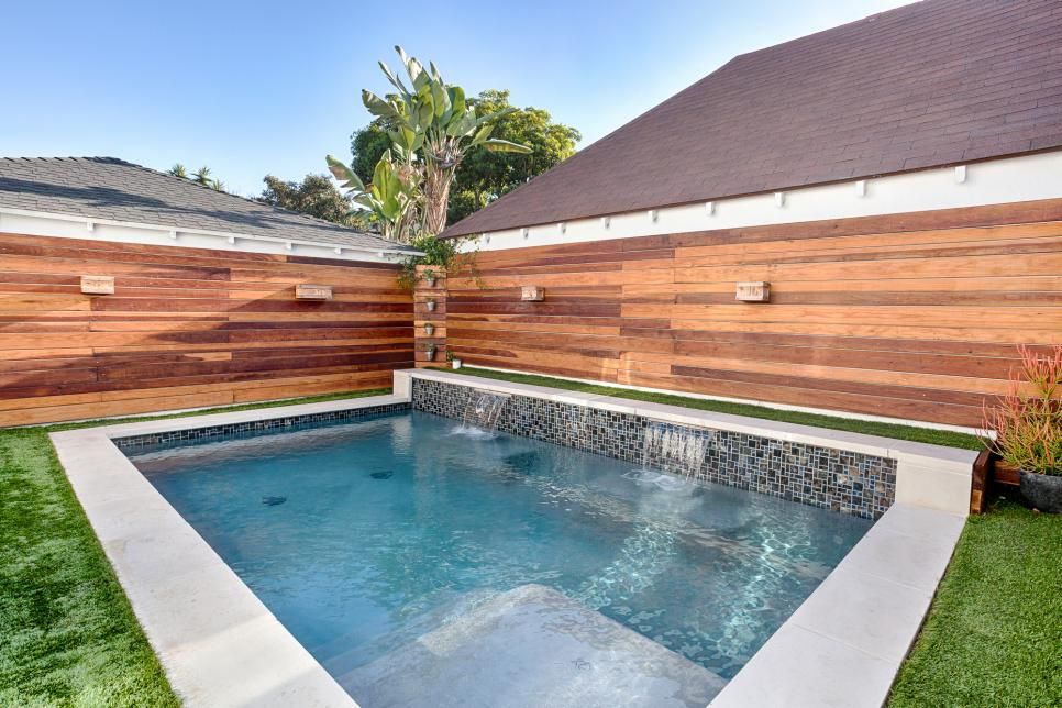 How's that for a blissful oasis? Nestled in the back corner of the yard, the swimming pool sparkles with a blue mosaic tile surround and two mini waterfalls.