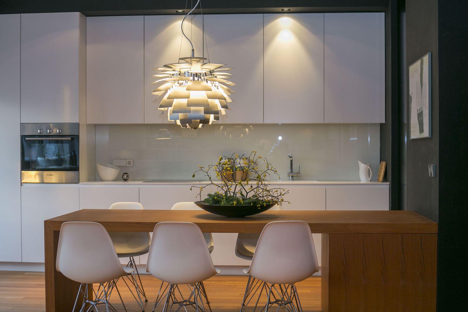 Bijela kuhinja; drveni stol u blagovaonici; bijele Eames stolice u ...