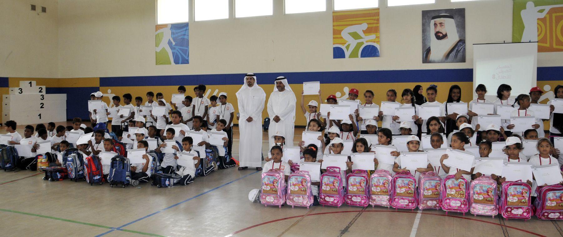 صورة جماعية لأعضاء وممثلي جمعية الشارقة الخيرية وجمعية الشارقة التعاونية مع الأطفال المشاركين بالمعسكر الصيفي الثامن