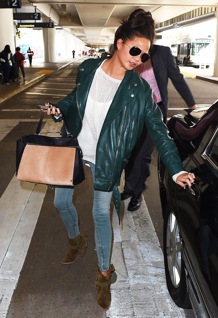 7008c96cdd7 Chrissy Teigen s chic travel style  oversized green leather motorcycle  jacket and brown suede boots