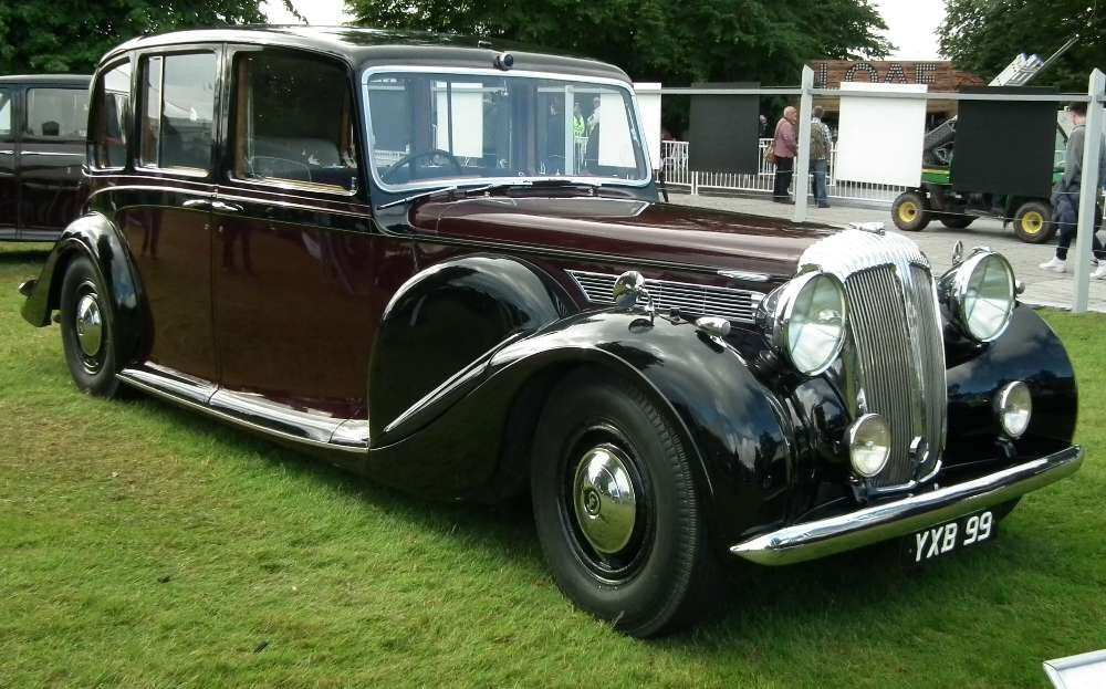 Fine. You must take the (1947) Daimler (DE 36 limousine landaulet) which carries a royal crest on its radiator -- I bought the thing years ago because it eased traffic at the feria in Sevilla -- and a chauffeur and a footman.