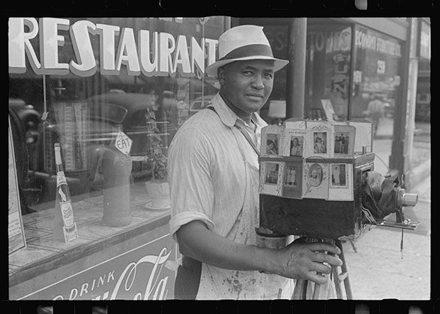 A traveling photographer shooting in Columbus, Ohio with his sidewalk portrait camera, 1938.