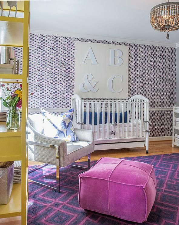 Pink and purple nursery features wallpapered accent wall