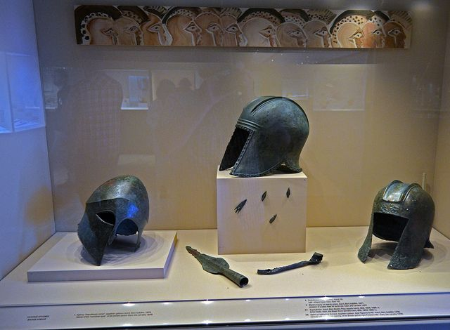 Archaic bronze armor from the area of Aiane  L to R: Corinthian-type helmet, bronze, Aiani, loc. Leivadia, Illyrian-type helmet, bronze, Agia Paraskevi,  Illyrian-type helmet, bronze, Aiani, loc. Leivadia Bronze arrowheads, leaf-shaped spearpoint, and imitation spearpoint, Aiani, various locations.  Archaeological Museum of Aiani/Αιανή