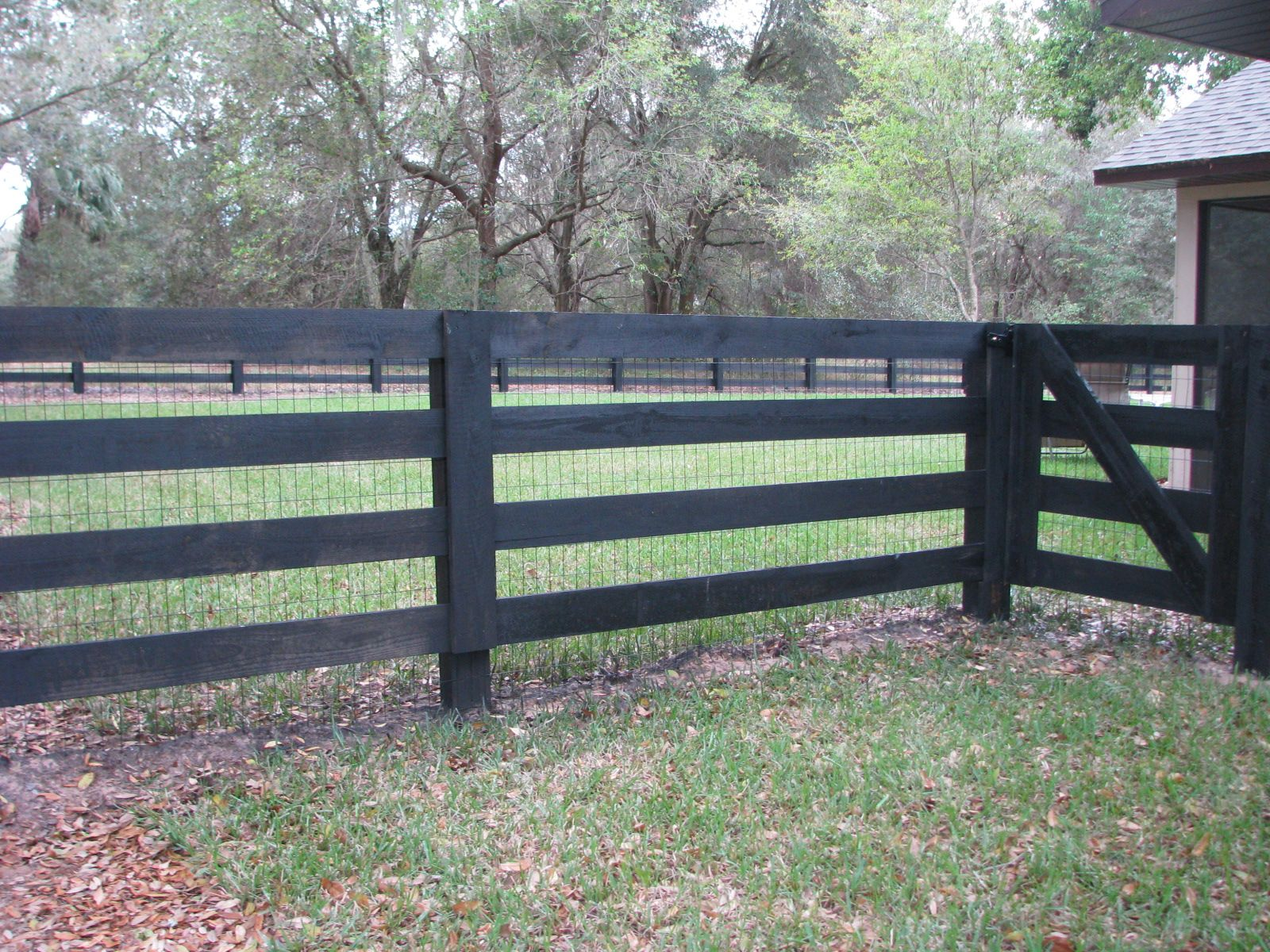 custom black wood horse fence with wire for additional protection