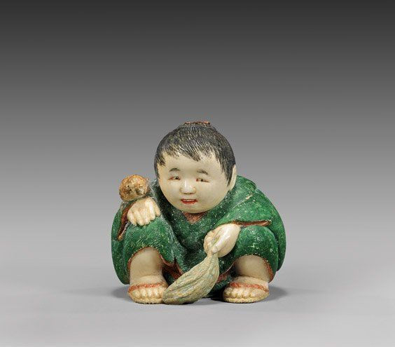 "CARVED & LACQUERED IVORY NETSUKE ~ ""Boy"" Finely carved and polychrome lacquered ivory netsuke; of a boy squatting low to the ground, holding leaves and with a bird on his hand, wearing a green kimono; signed Ichiro in red oval reserve"