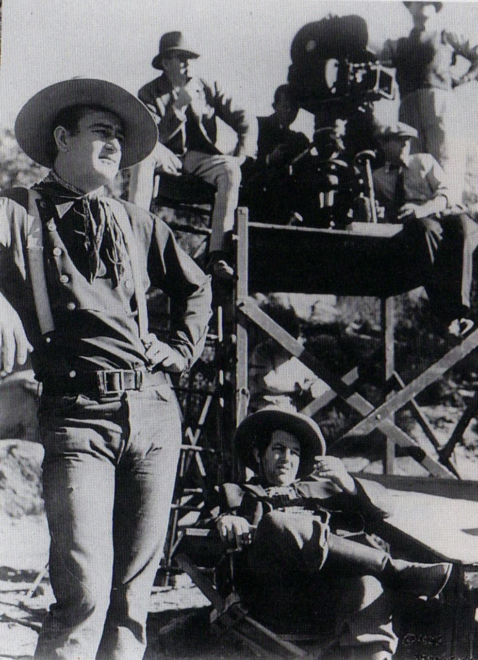 STAGECOACH (1939) - John Wayne & Andy Devine (seated in foreground) wait for the next scene.  Director John Ford is seated adjacent to the camera - Produced by Walter Wanger