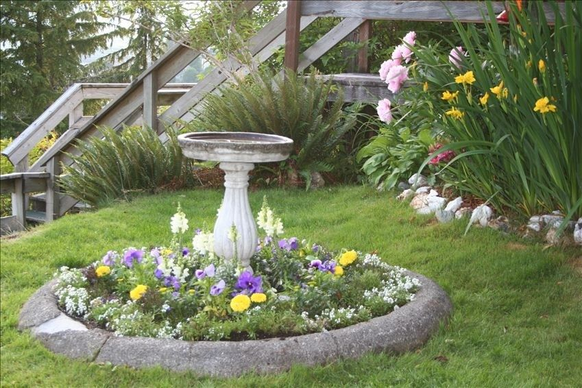 Curb Appeal: Bird Bath In Front Yard Surrounded By Flowers.