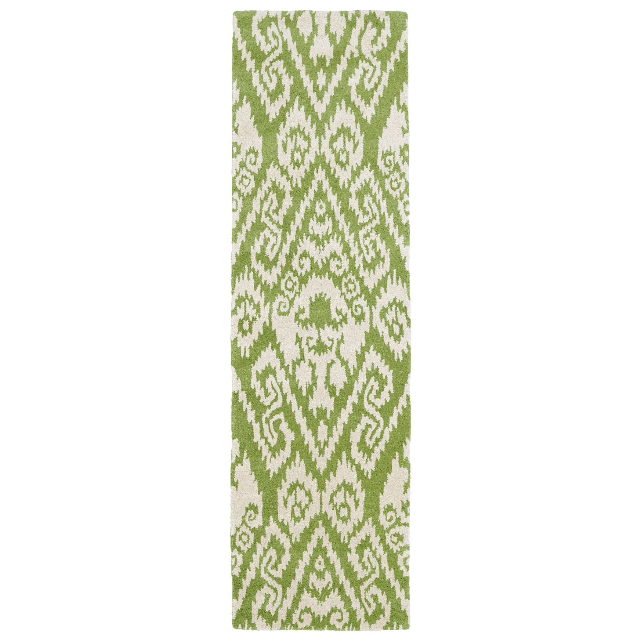Spice up your home decor with the Runway runner rug, crafted with 100-percent wool for comfort and style. With a cotton canvas backing to provide additional stability, this striking transitional rug decorates the home with a green and ivory ikat pattern.