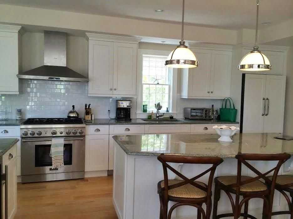 Nantucket kitchen has center island and an island with bar ...