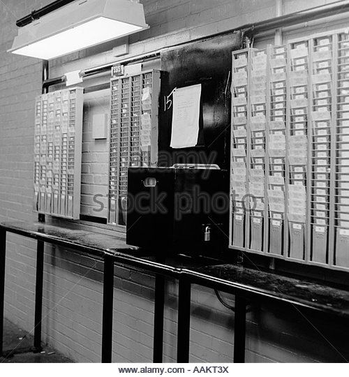 1960s TIME CLOCK \ CARD SLOTS IN LARGE FACTORY - Stock Image - time card