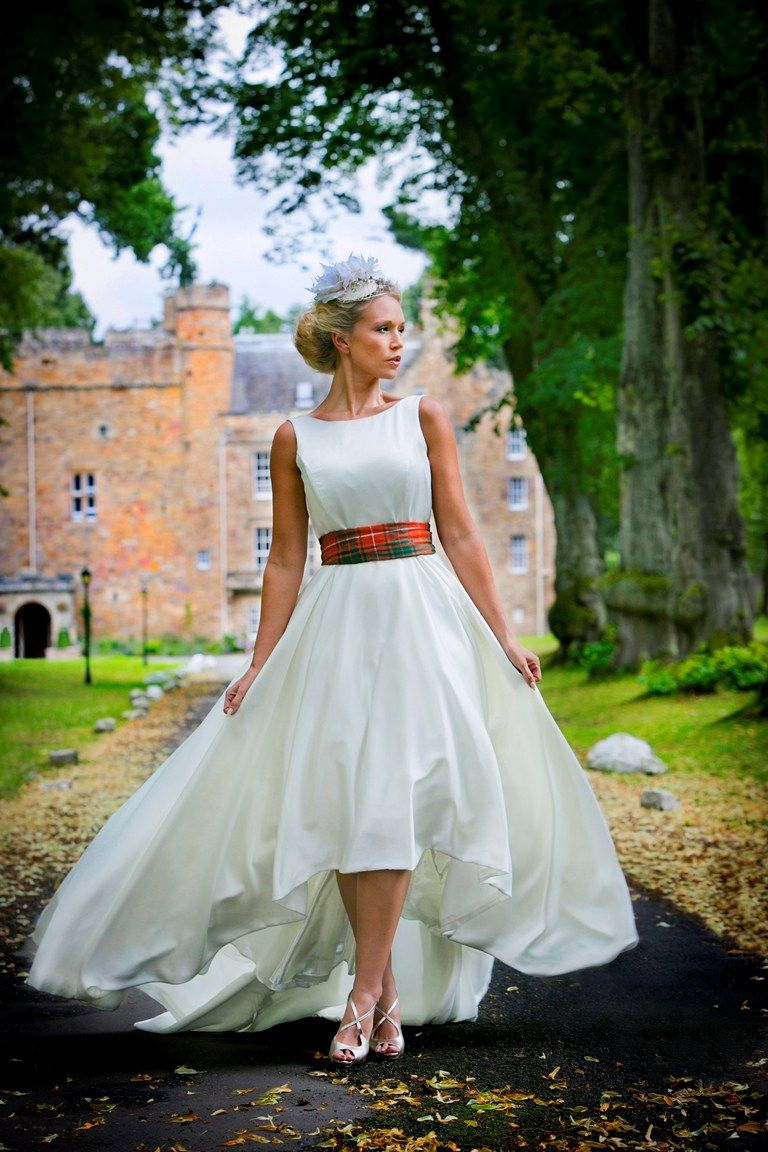 Scottish bride with castle in the background. Notice her tartan waist band on an all white wedding dress. Romantic Scottish Wedding. Photo: celticcastles.com
