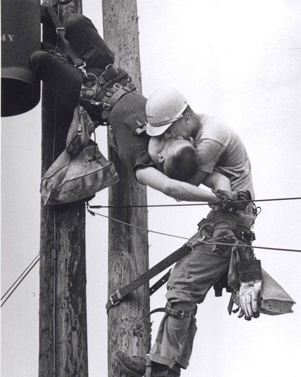 """""""The Kiss Of Life"""" Electrical Line Man gives mouth to mouth to his co-worker after he had his heart stopped by electrocution.This intervention saved his life.He was eventually brought to the ground and revived by cpr by the time paramedics came. 1967."""