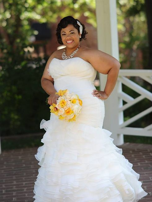 BBW holding yellow flowers while wearing a pretty strapless wedding ...