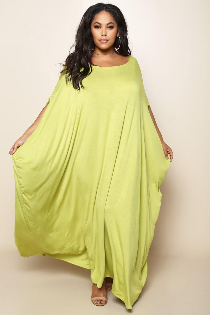 A plus size maxi dress with a boat neckline features two arm