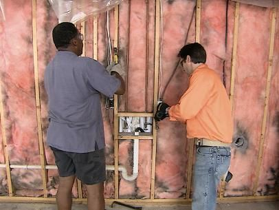 Two men Removing Nails From Studs