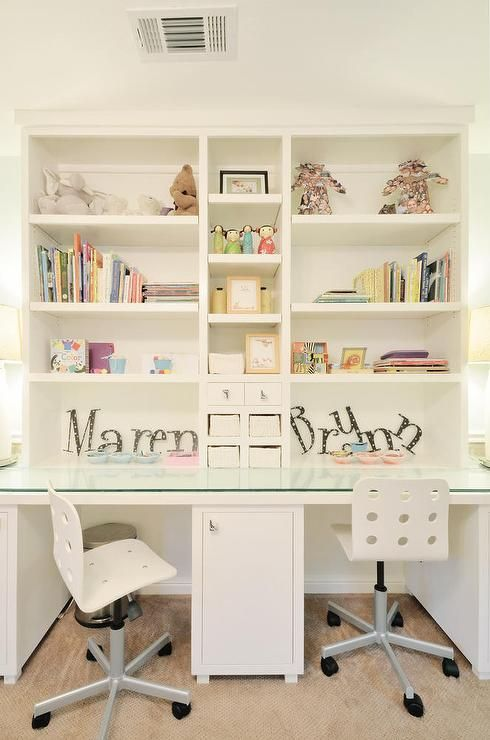 Shared girls  room features a built in white desk boasting a glass     Shared girls  room features a built in white desk boasting a glass top and  seating two white rolling desk chairs in front of white shelves accented  with