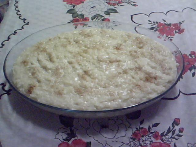 1 litro de leite frio  - 2 litros de água fria  - 2 1/2 xícaras de chá de arroz  - 5 unidades de cravo-da-índia  - 2 unidades de canela em pau  - 2 latas de leite condensado  - 100g de coco ralado  - Canela em pó para polvilhar  -