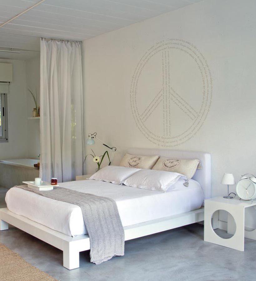 En la suite, la cama tiene una base blanca de madera, respaldo con ...