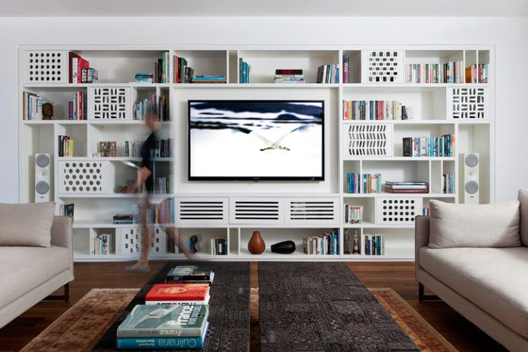A Wall Of Custom Designed Shelving Was Added To This Apartment Shelving Units Living Room Living Room Wall Units