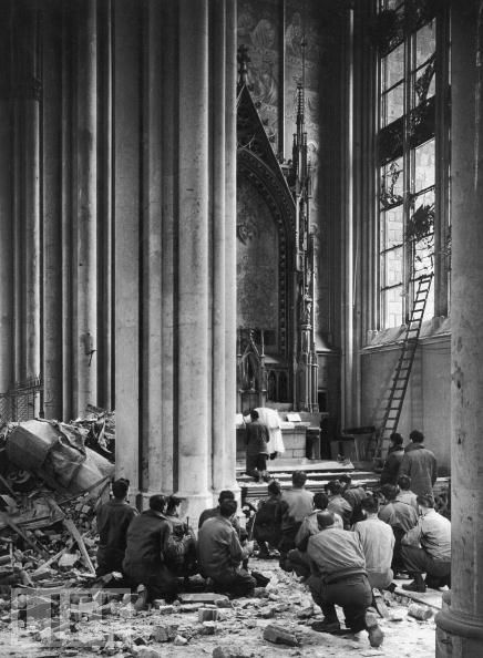 World War II: Church Service in Cologne Cathedral, 1945  An American Army chaplain leads a group of kneeling soldiers (still armed with rifles) in prayer in Germany's famous Cologne Cathedral. Margaret Bourke-White photograph.