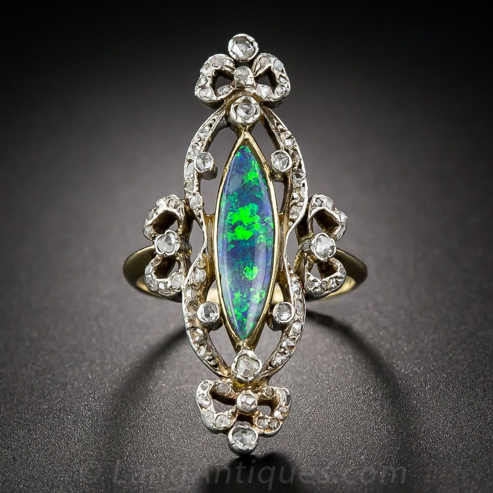 Victorian Opal and Diamond Ring. 'Unique, regal and enchanting' are just a few adjectives that will come to mind when you behold this 'exquisite' (there's another one!) antique jewel. A long and slender navette-shape black opal, aglow with a cool-colored palette of blues and greens, is fancifully wrapped all around in glittering rose-cut diamond bows. The opal setting and ring shank are in 18K yellow gold, the diamonds are set in silve