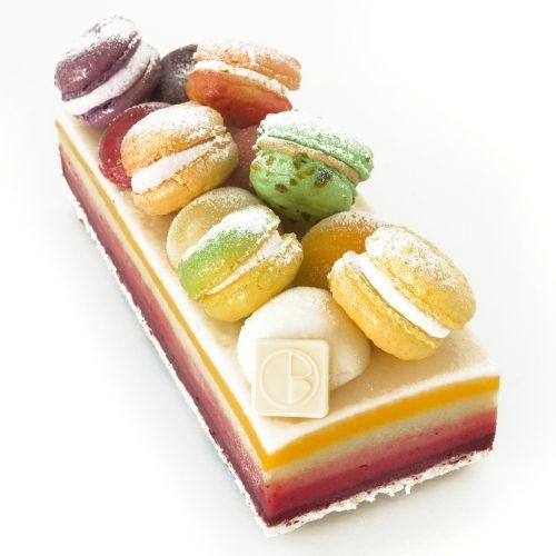 L'Arc en Ciel. Six sorbets superposés : citron, fruits exotiques, pomme, fraise, framboise et cassis. Biscuit dacquoise aux amandes. Macarons variés et boules en décor. Olivier Bajard