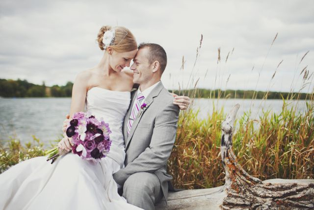A sweet wedding photo of the bride and groom by the lake