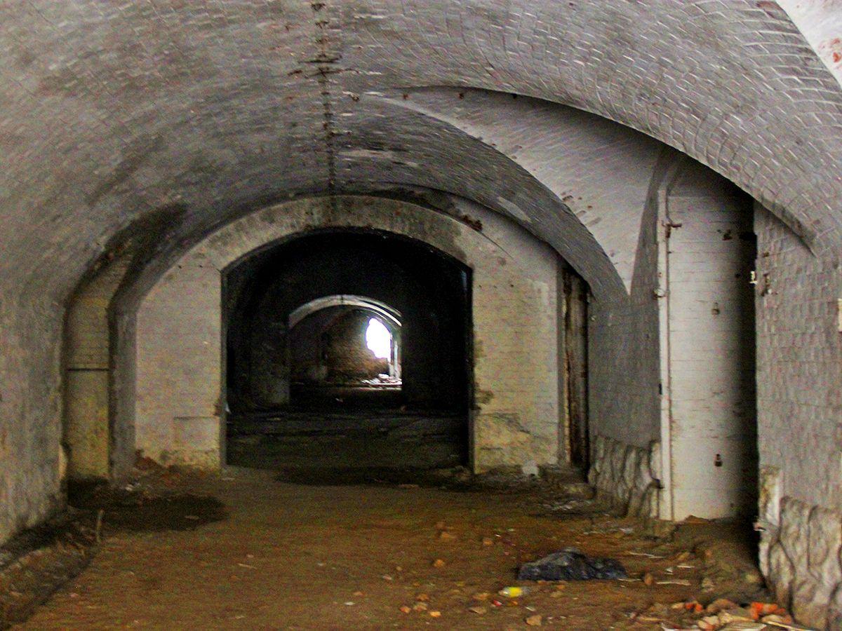 Побеленные коридоры, вдалеке проход частично заложен кирпичом