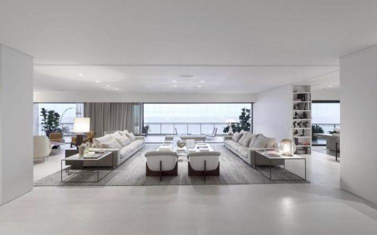grand salon blanc et moderne avec deux canapés en blanc et gris clair et un tapis gris