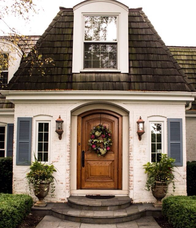 Whitewashed brick, wood door, and blue shutters on this entry ...