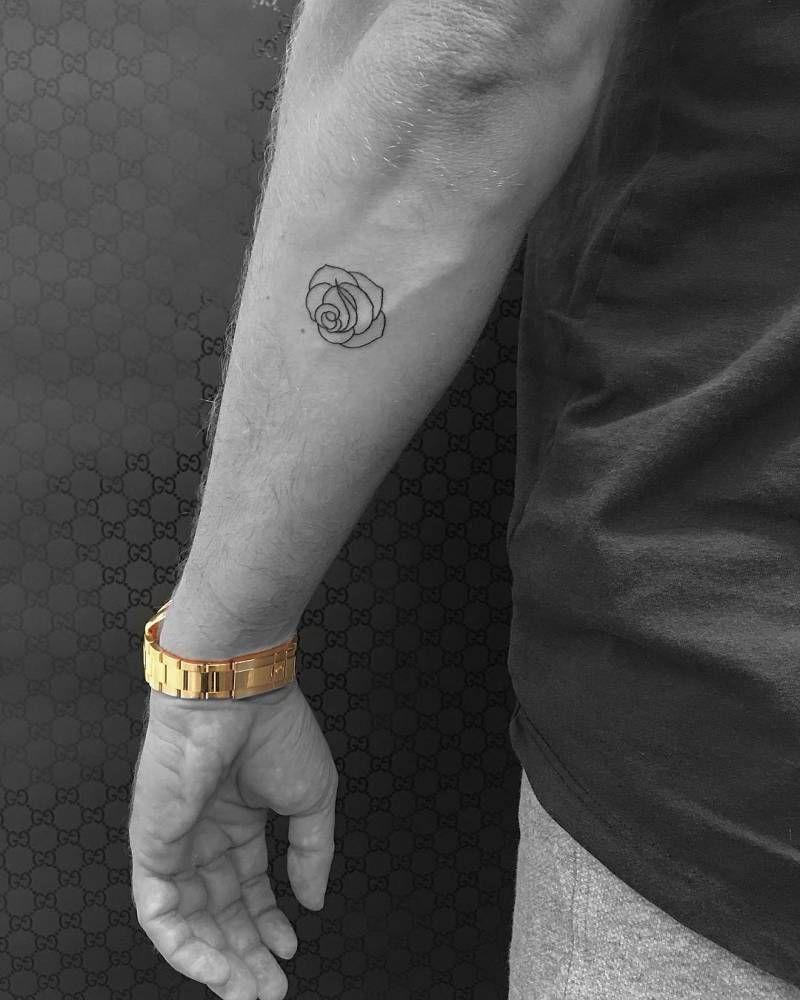 Minimalist rose tattoo on the left forearm.