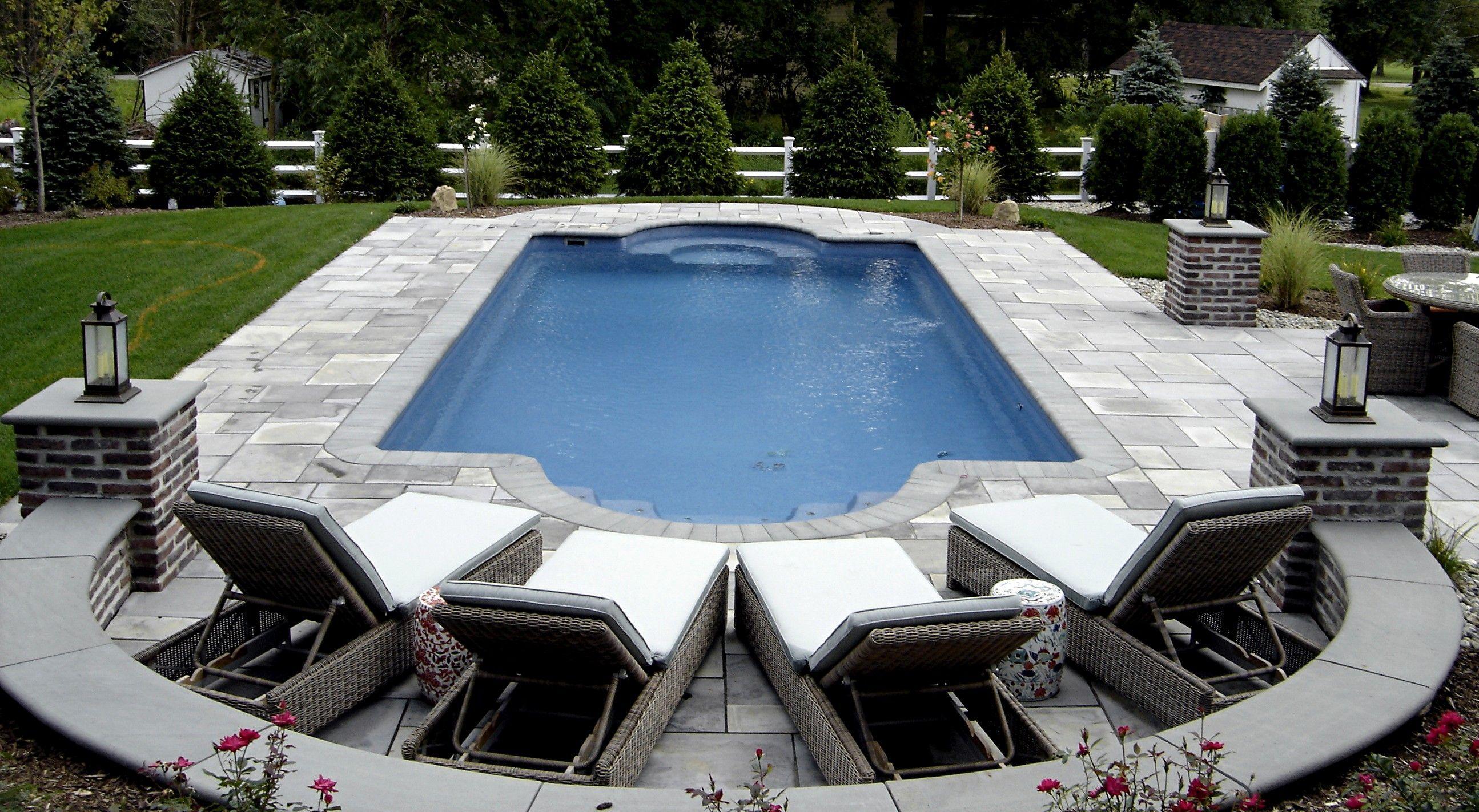 Formal shape fiberglass pool with brick and bluestone columns and ...