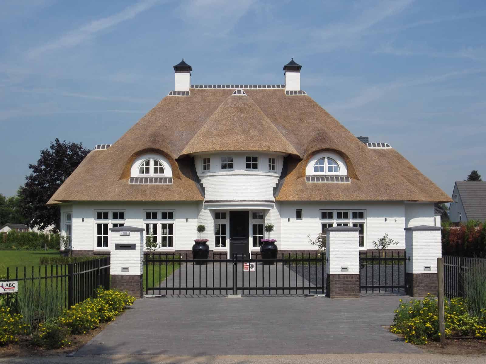 Statige symmetrische witte villa met riet te bathmen