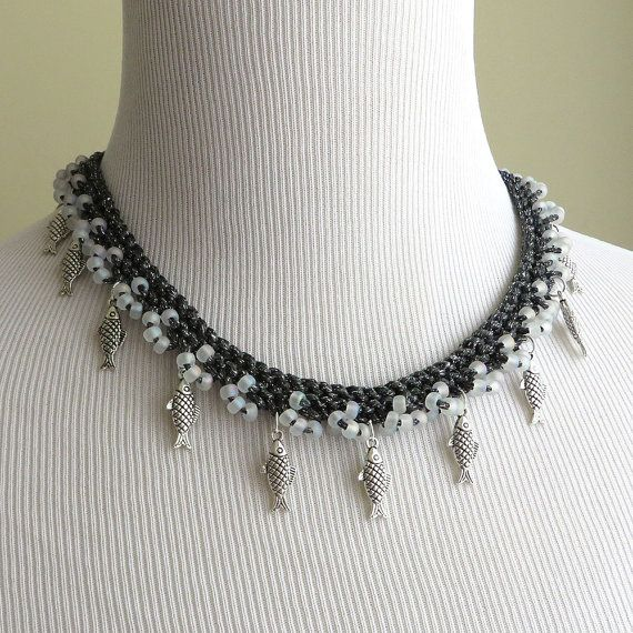 Handknit necklace in dark grey with translucent beads and metal fish charms