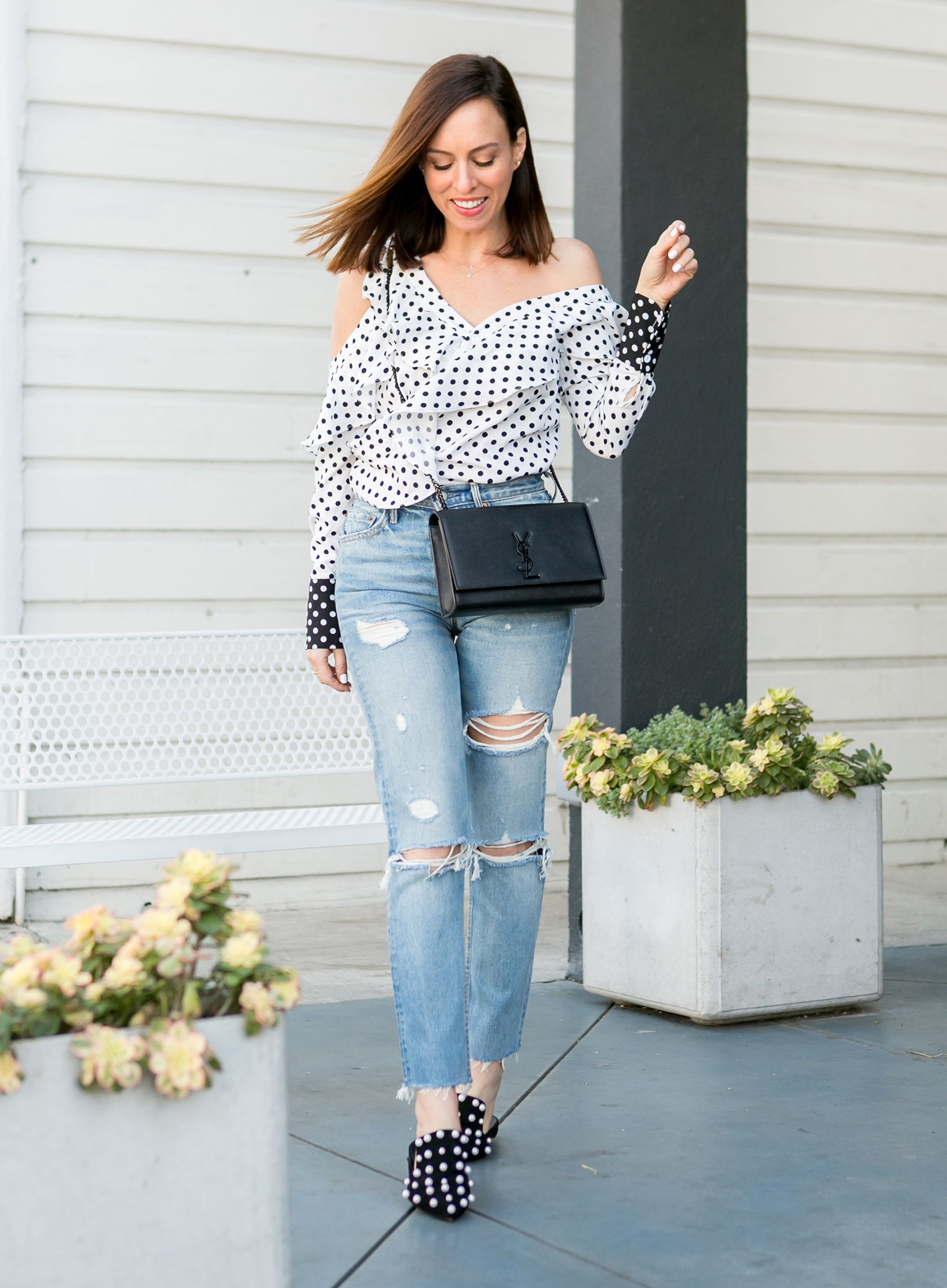 0903375350 Sydne Style shows how to wear the asymmetrical shirt trend for spring in shein  polka dot top #pearls #polkadots #denim #jeans #springtrends #ysl