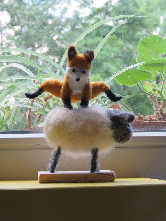 Fuchs springt Schafe in gefilzter Wolle.