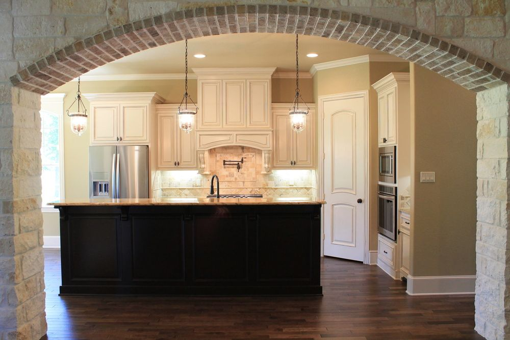 Stone Arched Entry To Kitchen White Glazed Cabinets With