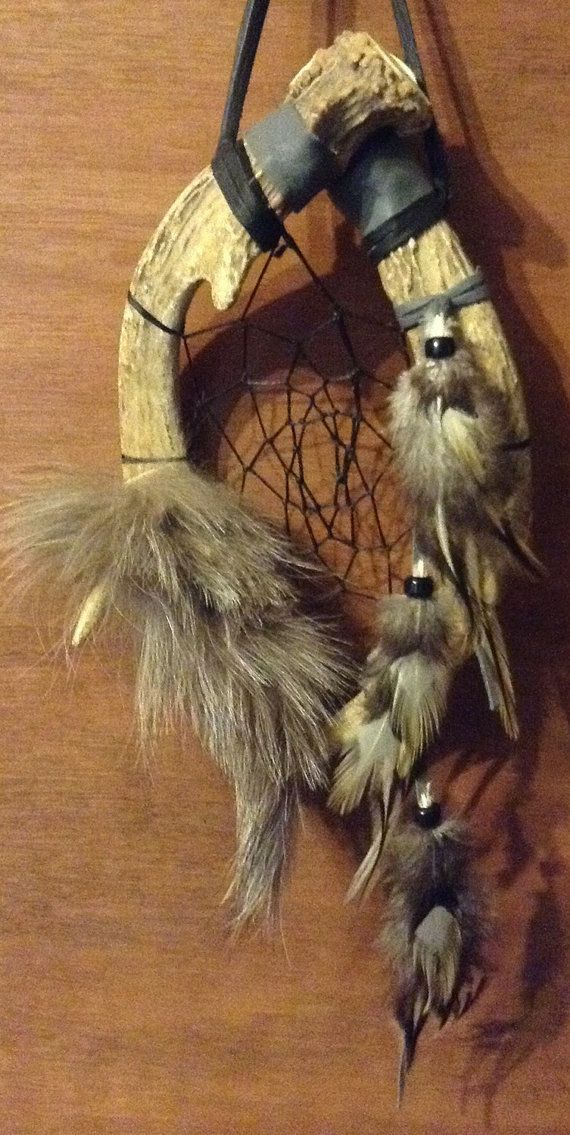 This dream catcher is made with 2 deer antlers has black artificial sinew webbing has silver fox fur attached at the bottom and rooster feathers attached with glass beads measures 6 1/2 in. wide And 17 in. long has a total of 4 points (2 under fur)
