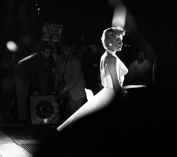 """Marilyn Monroe between poses during the famous subway grate scene from """"The Seven Year Itch"""",1954, photographed by George Zimbel."""