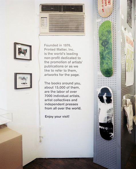 Skateboard decks and framed art hung on white walls