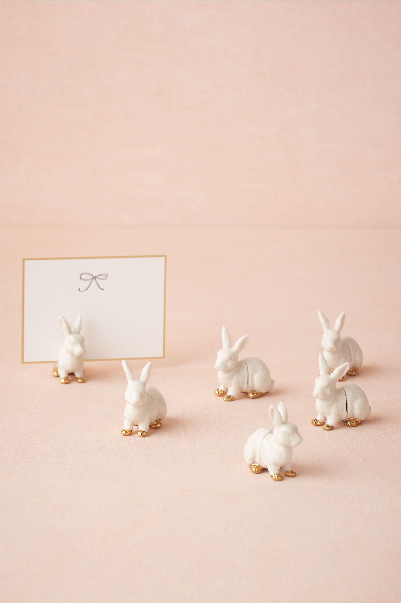 "Bunny Place Card Holders (6)  $28.00  Sweet cottontails dressed up with gilded paws guide guests to their assigned seats. A magnet closure allows you to pull them apart to slide place cards in. Available exclusively from BHLDN.        Set of 6      1.75""H, 1.5""W      Stoneware, magnet      Spot clean      Imported"