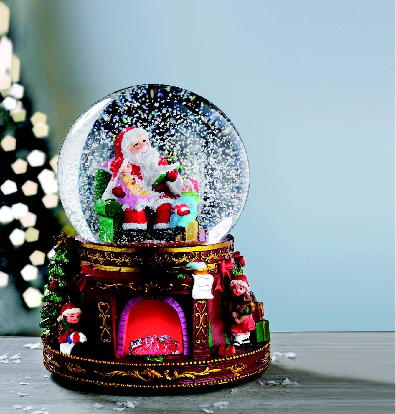 A musical snow globe with santa and christmas tree scene complete