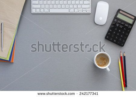 View from above on the office working place at morning. Well organized workspace on the grey wooden table with keyboard, pens, coffee mug and other business supplies