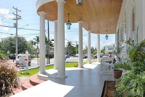 Symmetrical wrap-around porches with tall round columns.