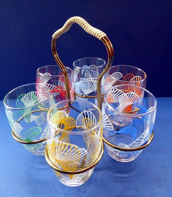 Very sweet little set of mid century drinking glasses or wee tumblers - probably best for little summer cocktails. The set consists of six little glasses - each with a swirlng atomic design on them, rather like a pattern that you might create with Spirograph.  The glasses are all in different tutti frutti colours, but with the same abstract pattern.  Each glass has no damges.  The glasses fit into a little metal stand, as photographed. Great addition to your cocktail cabinet. Fair price for…