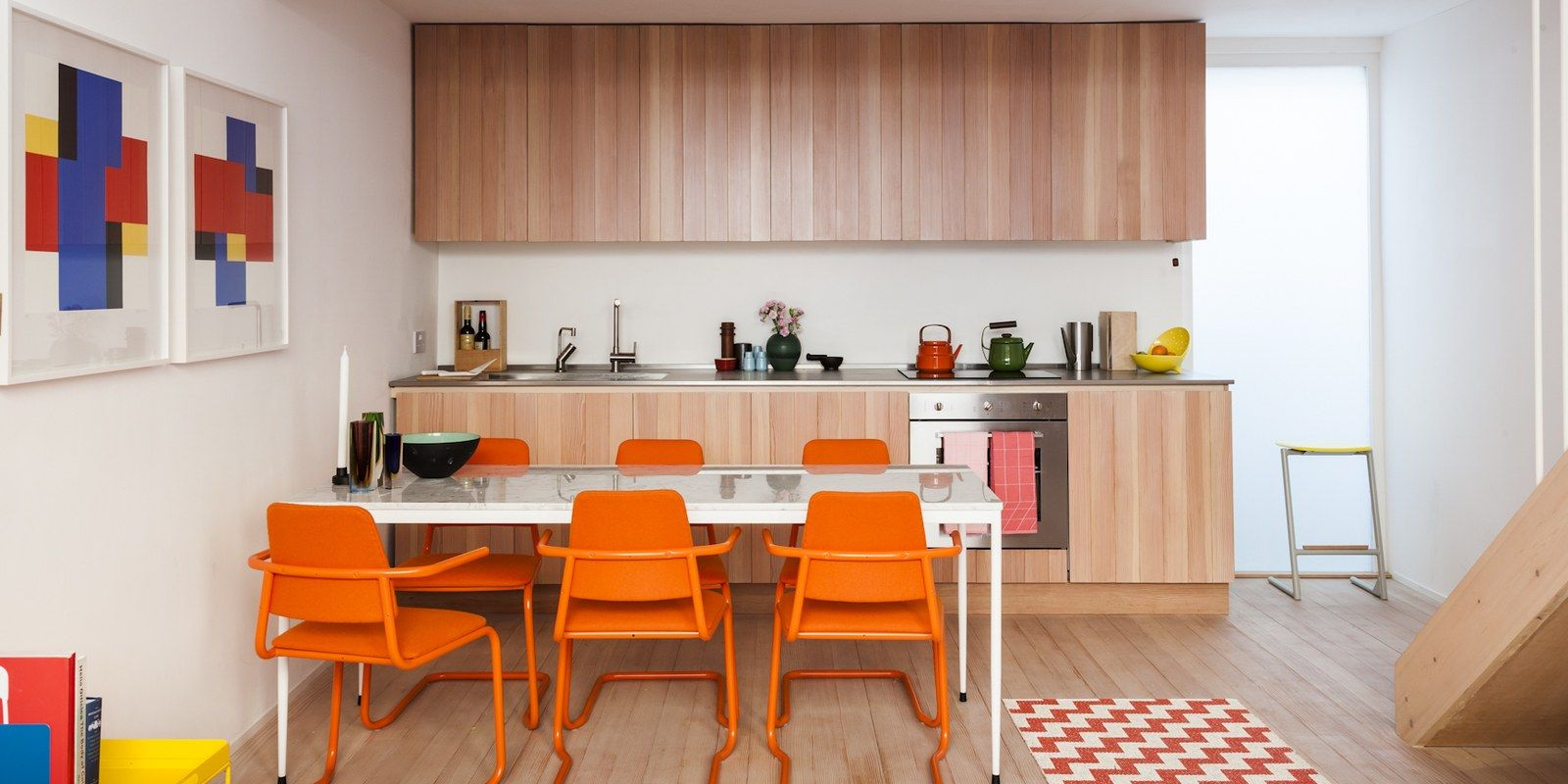 Eat in kitchen with wood paneled cabinets and orange dining chairs
